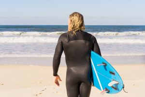 man with surf board on the ocean shore. Surfer in a wet suit.